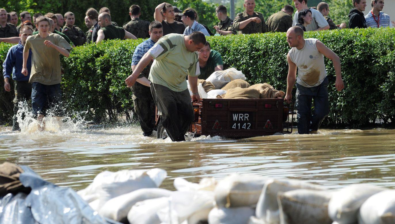 """W 2010 roku, trzynaście lat po """"powodzi tysiąclecia"""", Wrocław ponownie zalała woda. Mieszkańcy osiedla Kozanów usiłowali zabezpieczyć swoje domy przed zalaniem przez rzekę Ślęzę, która wystąpiła z brzegów na skutek cofki Odry. Fot. PAP/Grzegorz Hawałej"""