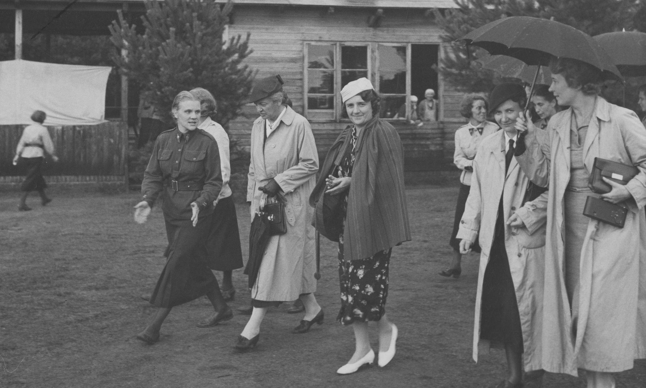 Obóz Przysposobienia wojskowego Kobiet w Borkach w 1937 roku. Na zdjęciu: Aleksandra Piłsudska (w jasnym płaszczu) i Maria Mościcka (w białym toczku) wśród uczestniczek szkolenia. Komendantka Naczelna Przysposobienia Wojskowego Kobiet Maria Wittek druga z prawej (pod parasolką). Fot. NAC/IKC, Witold Pikiel, sygn. 1-W-2509-1
