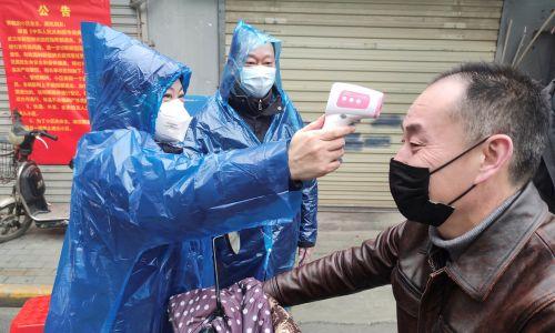 Wracając z miasta na osiedle, trzeba wypełnić formularz, gdzie się było i zmierzyć temperaturę. Fot. China Daily via REUTERS