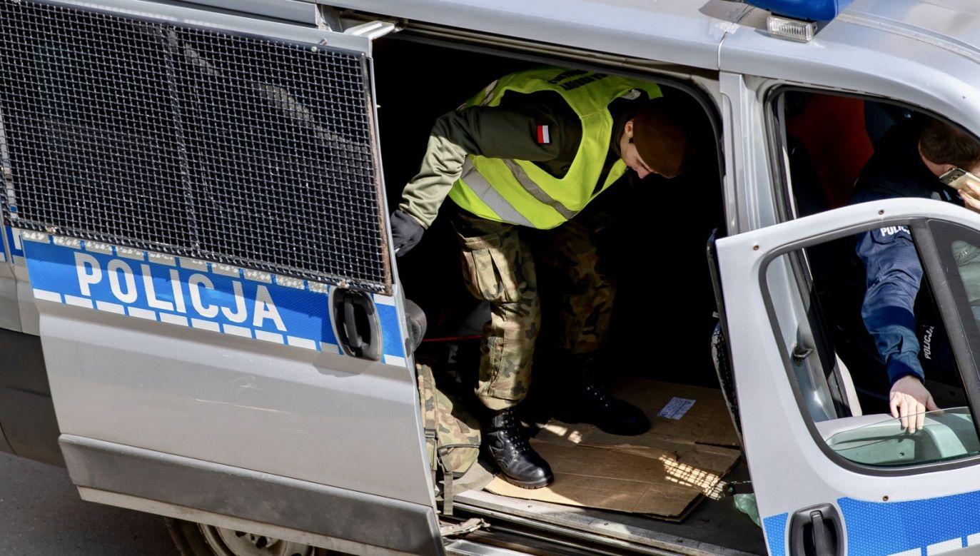 Patrol policji z żołnierzami WOT sprawdza obecność osoby przebywającej na kwarantannie, 26 bm. w Łodzi (fot. PAP/Grzegorz Michałowski)