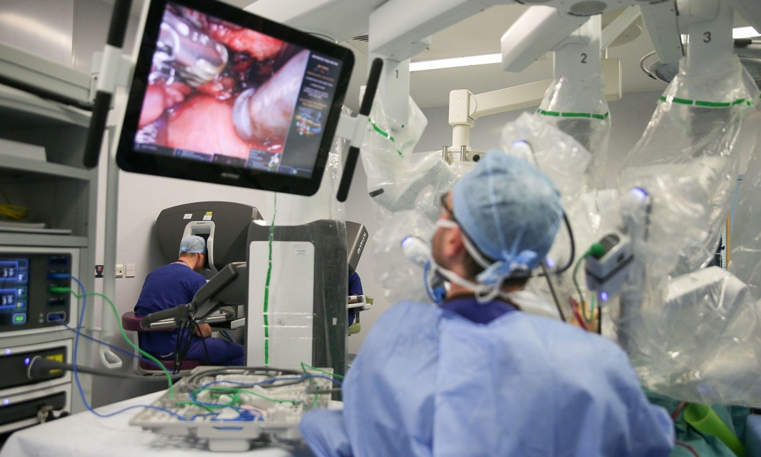Chirurg Vin Paleri (po prawej) za pomocą rpbota da Vinci przeprowadza minimalnie inwazyjną operację hemiglossektomii podstawy języka na 67-letniej pacjentce Anne White, styczeń 2018 roku. Zabieg w Royal Marsden Hospital w Londynie obserwuje na konsoli William, książę Cambridge (po lewej), który odwiedził placówkę, by obejrzeć dwie pionierskie, zrobotyzowane operacje. Fot. Daniel Leal-Olivas - WPA Pool / Getty Images