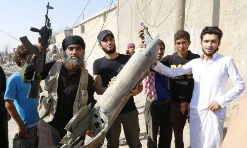 Bojownicy ISIS z kawałkami syryjskiego samolotu strąconego nad miastem, 16 września 2014. Fot. REUTERS/Stringer