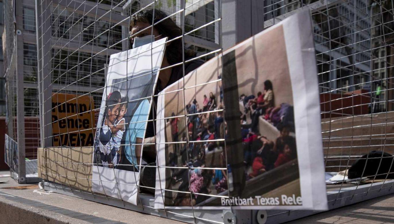 Protest aktywisty w Los Angeles otoczonego zdjęciami uwięzionych rodzin migrantów  (fot. PAP/EPA/ETIENNE LAURENT)
