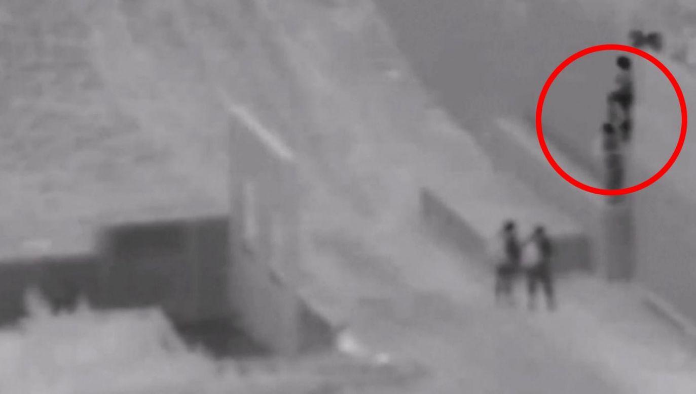 Dziecko zrzucane z muru granicznego (fot.  EBU/@USBPChiefSDC)