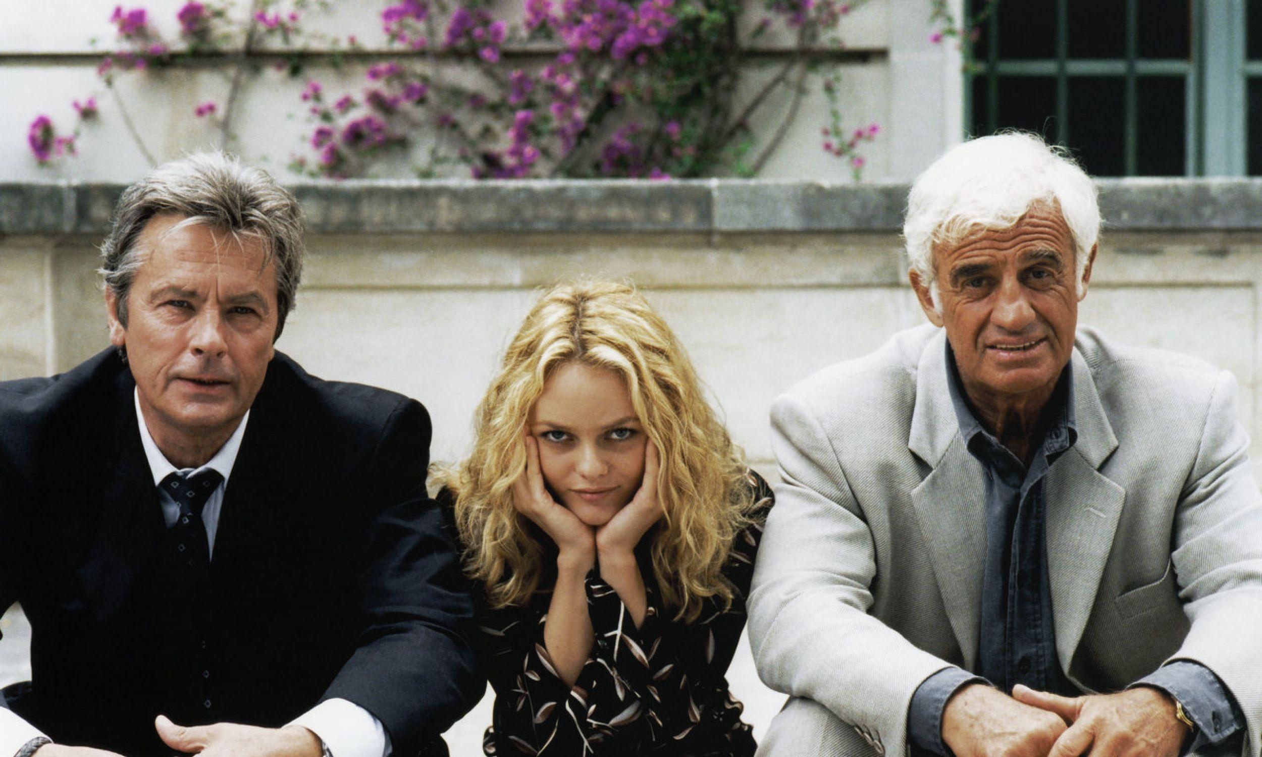 """Kochały ich panie na całym świecie, a wokół gromadziły się te najpiękniejsze. Prasa francuska polowała na zdjęcia kolejnych kobiet, dzieci i wnuków obu gwiazdorów. Nie dopuszczali mediów blisko: Delon zamknął się w swojej posiadłości, Belmondo odtrącał fotografów, zwłaszcza gdy robili zdjęcia dzieciom. Tu: Alain Delon, Vanessa Paradis i Jean-Paul Belmondo na planie filmu """"Dziewczyna dla dwóch"""" (Une chance sur deux) w reżyserii Patrice'a Leconte. 1997 rok. Fot. Patrick CAMBOULIVE/Sygma via Getty Images"""