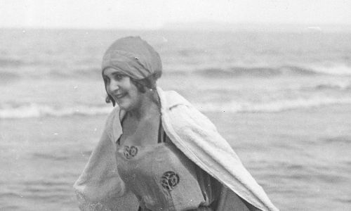 Drugi rodzaj stroju, bardziej ozdobny, składał się z tuniki do połowy uda, pod którą zakładano spodenki z jedwabiu. Strój ozdobiony był falbankami, kokardkami – dla kogoś, kto cenił sobie elegancję, a nie sportowy szyk. Bardziej służył do pluskania się w wodzie i leżeniu na plaży, niż do pływania. Na zdjęciu kobieta na plaży w stroju kąpielowym, ciepłej pelerynie i czepku na głowie. Lata 1918 – 1939. Fot NAC/IKC, sygn.1-M-2943-13