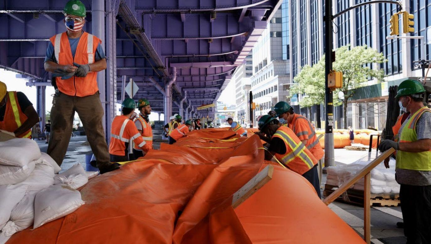 Pracownicy wznoszą tymczasowe bariery przeciwpowodziowe w sąsiedztwie South Street Seaport  w Nowym Jorku (fot. Spencer Platt/Getty Images)